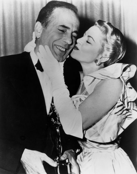 1952: American actor Humphrey Bogart (1899-1957) receives a kiss from actor Claire Trevor (1909 - 2000) while standing backstage with the Best Actor Oscar he won for his role in director John Huston's film, 'The African Queen,' RKO Pantages Theatre, Los Angeles, California. (Photo by Hulton Archive/Getty Images)